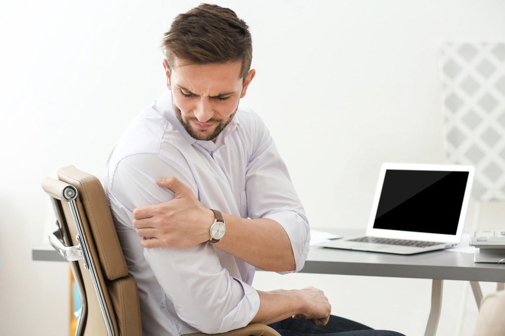 Man suffering from shoulder pain at work