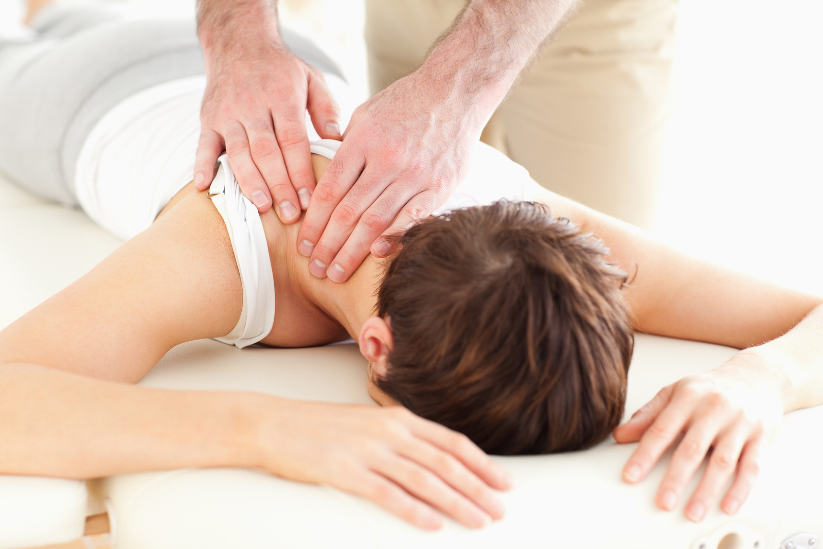 woman is getting back and neck pain treatment